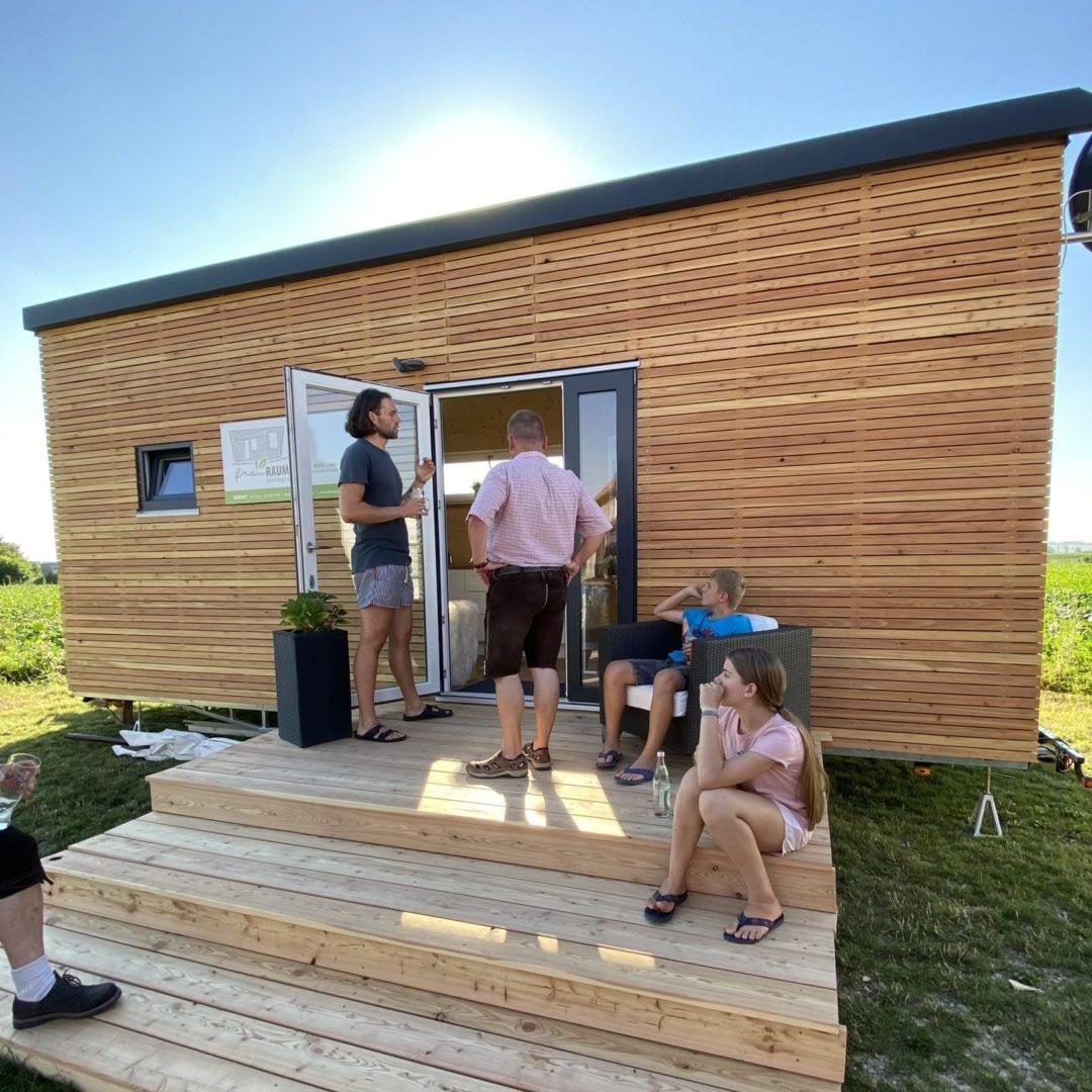 Tiny House mit Besuchern auf der Terrasse